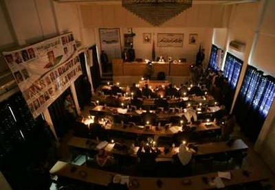 Palestinian lawmakers attend a parliament session in candlelight during a power cut in Gaza January 22, 2008. Israel agreed to allow some fuel, medicine and food into the Hamas-run Gaza Strip on Tuesday, at least temporarily easing a blockade that has plunged much of the territory into darkness and sparked international protests. REUTERSMohammed Salem (GAZA)