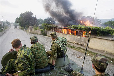 Russian soldiers on top of an APC pass by a burning house on the way to Tskhinvali, capital of Georgian