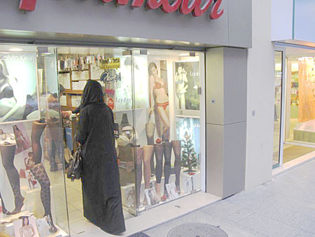 Veiled women entering a lingerie store